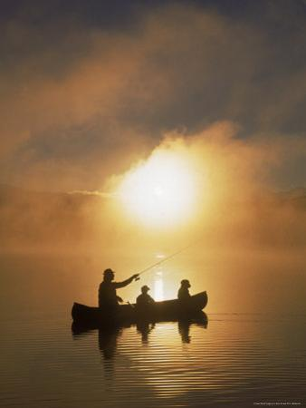 People Fishing from Canoe at Sunset