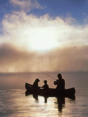 Silhouetted Father and Son Fishing from a Canoe by Bob Winsett