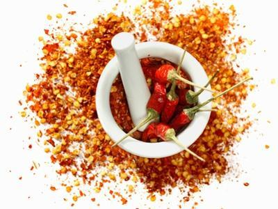 Dried Chilli Peppers and Chilli Flakes in a Mortar by Bodo A. Schieren
