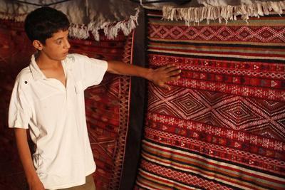 https://imgc.allpostersimages.com/img/posters/boy-showing-a-rug-in-a-carpet-shop-toujane-tunisia_u-L-Q1GYKKV0.jpg?artPerspective=n