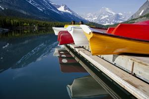 Glacier, Montana: Colorful Canoes Line the Dock at Many Glacier Lodge on Swiftcurrent Lake by Brad Beck