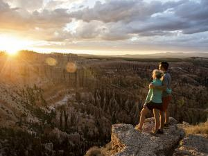 A Couple at Sunset in Bryce Canyon National Park in the Summer Overlooking the Canyon by Brandon Flint