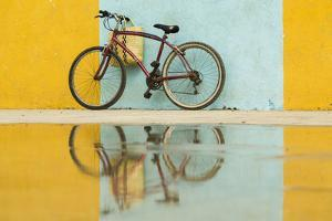 Cuba, Trinidad. Bicycle and reflection against yellow and blue walls. by Brenda Tharp