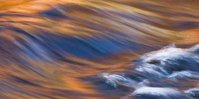 Painterly Impression of a rushing stream reflecting autumn colors. by Brenda Tharp
