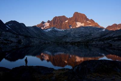 A Male Hiker Is Silhouetted in Garnet Lake Along the John Muir Trail in California