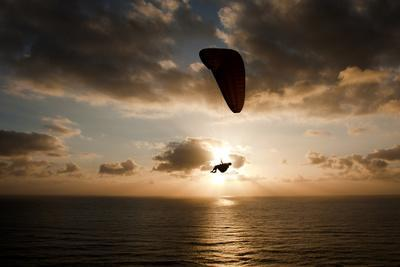 A Paraglider Crosses the Path of the Sun at the Torrey Pines Gliderport in San Diego, California