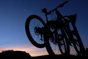A Silhouette of Two Mountain Bikes on Car Rack in Red Rock Canyon in Nevada by Brett Holman