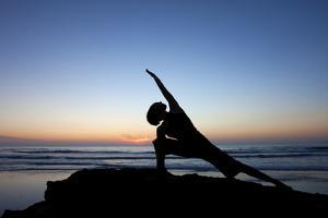A Young Woman Performs Yoga at Blacks Beach in San Diego, California by Brett Holman