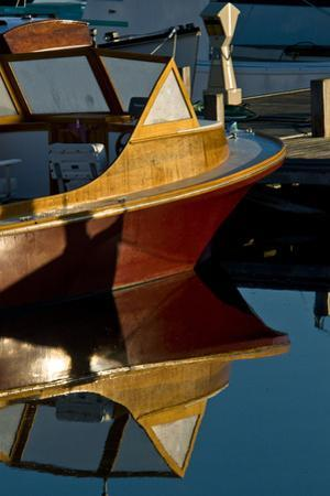 An Antique Powerboat Reflected in the Calm Water of Bass Harbor, Maine by Brian Gordon Green
