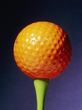 An Orange Golf Ball on a Green Tee with a Blue Background by Brian Gordon Green