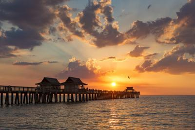 Setting sun over the Naples Pier and Gulf of Mexico, Naples, Florida, USA by Brian Jannsen