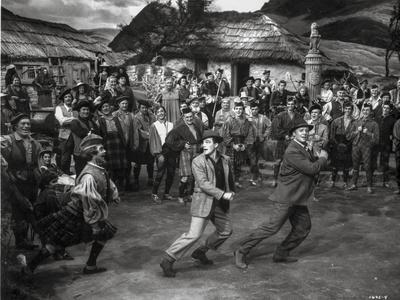 https://imgc.allpostersimages.com/img/posters/brigadoon-excerpt-three-men-dancing-in-a-crowd_u-L-Q11614B0.jpg?artPerspective=n