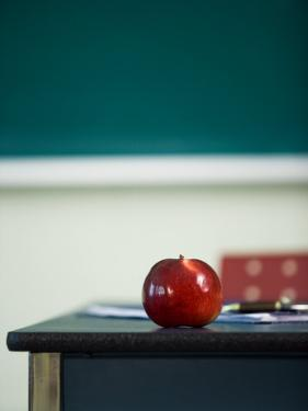 Bright Red Apple on Desk of Teacher in Classroom