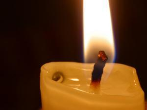 Bright Warm Flame and Melting Wax on Lit Candle
