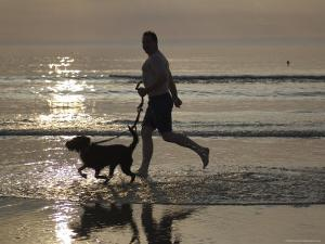 Silhouette of Man Running with Dog on Beach, Sunset, Romo, Denmark by Brimberg & Coulson