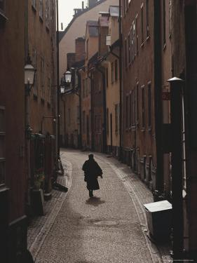 Sweden, Stockholm, Woman Walking on Narrow Streets of Gamlestaden, Rear View by Brimberg & Coulson