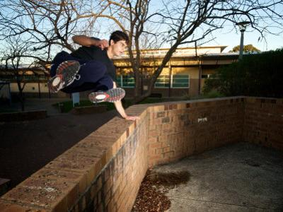 Jack Belle, a Traceur Vaulting a Wall Using Parkour in Urban Jungle