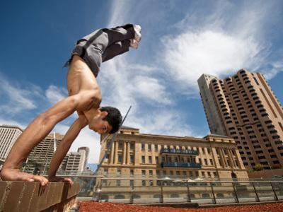 Male Gymnast Does a Handstand on the Edge of Wall in Cityscape