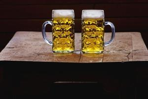 Two Glass Mugs of Beer on Table by Bruno Ehrs