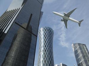 Commercial Jet Flying over Skyscrapers by Buena Vista Images