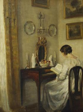 An Interior with a Girl Reading at a Desk by Carl Holsoe