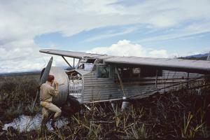Aviator Roland Angel Repaints His Father's Flamingo Monoplane, Auyantepui, Venezuela, 1965 by Carl Mydans