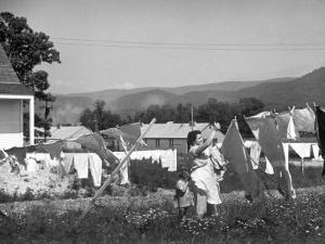 Housewife in Tygart Valley Removing Laundry from Clothesline, Her Young Daughter Stands Beside Her by Carl Mydans