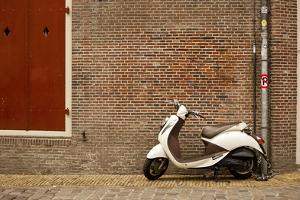A Scooter Parked on the Sidewalk Outside of Oude Kerk Church in Amsterdam, Netherlands by Carlo Acenas