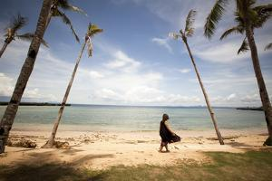 A Woman Walks with Her Shoes Off on the Beach Near the Exclusive Balesin Island Club, Philippines by Carlo Acenas