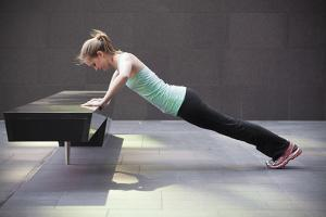 A Young Woman Does a Pushup on a Park Bench in San Francisco, California in Workout Apparel by Carlo Acenas