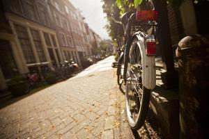 Bicycle in an Alley Street in Amsterdam, Netherlands by Carlo Acenas