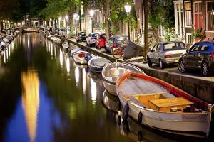 Boats in the Canal Near the Zuiderkerk Church in Amsterdam, Netherlands by Carlo Acenas