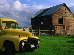 Old Barn and Yellow Pick-Up Truck in Montana, Montana, USA by Carol Polich