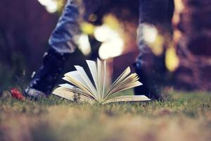 A Young Adult Standing over an Open Book by Carolina Hernández
