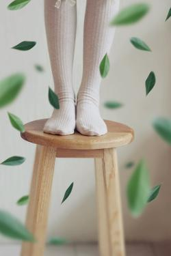 Young Woman Feet in Socks on a Stool by Carolina Hernandez