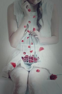 Young Woman Holding Small Bird Cage on Her Lap by Carolina Hernandez