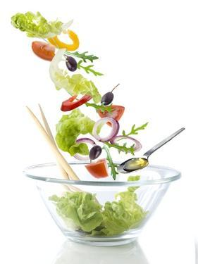 Salad Ingredients Falling into a Glass Bowl by Caroline Martin