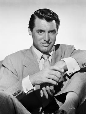 Cary Grant portrait in suit and tie holding hand by E Bachrach
