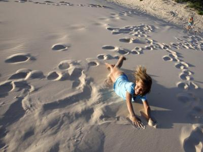 Young Girls Rolling Down Sand Dune
