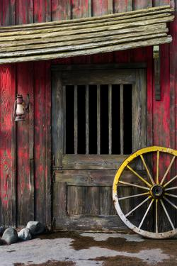 Detail of Old Wagon Wheel next to a Wooden Wild West Typical House by ccaetano