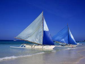 Boracay beach with traditional sailboats by Charles Bowman