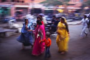 Indian women in colourful saris walk along streets by Charles Bowman