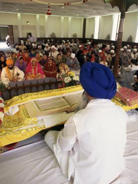 Sikh Priest and Holy Book at Sikh Wedding, London, England, United Kingdom by Charles Bowman