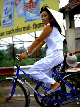 Vietnamese woman cycles in white clothes and hat by Charles Bowman