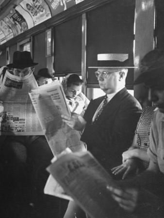 Commuters Sitting on a Train and Reading the Chicago Tribune by Charles E. Steinheimer