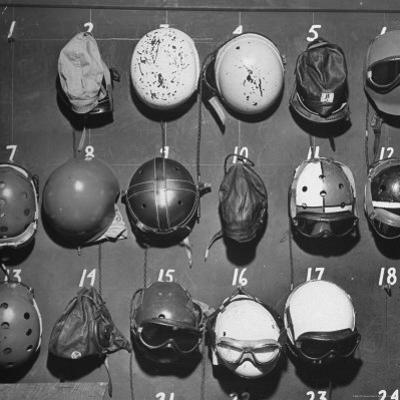 Jet Pilot Helmets and Goggles Hanging on Hooks by Charles E. Steinheimer