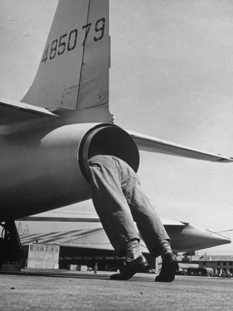 Mechanic Climbing Into Tailpipe to Check Clearance Between Turbine Wheel Bucket Tips and rug by Charles E. Steinheimer