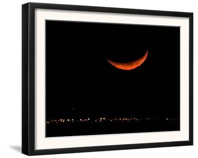 A Crescent Moon Dwarfs the Lights of Fort Riley Army Base in Central Kansas, January 22, 2007