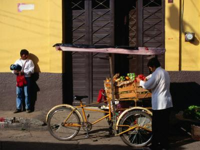 Street Vendor with Bicycle Cart Laden with Fruit and Vegetables, Mexico by Charlotte Hindle