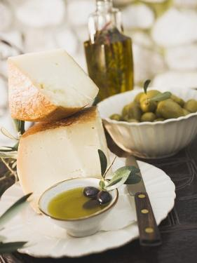 Cheese, Olives and Olive Oil on Table Out of Doors